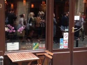 The queue of people lining up to get into Frenchie's bar, seen in a reflection on a window of Frenchie's restaurant, just across the alley