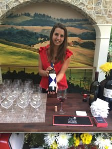 Sommelier Margaux shows off the Gaja Ca'Marcanda Promis 2013 she is pouring at the Italy pavilion